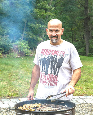 Chef and restaurateur Jay Hajj at his back-yard grill. (Photo by Ken Goodman)