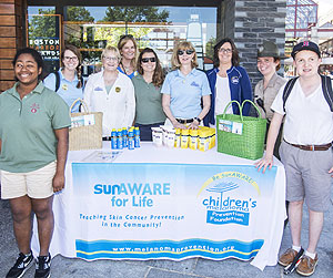Smiling for the camera are summer interns from the Perkins School for the Blind along with staff from the Children's Melanoma Prevention Foundation, the Boston Harbor Islands Welcome Center and the Department of Conservation and Recreation. (Photo by Scott Eisen)